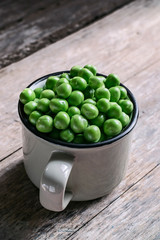 Dried Green Peas in a vintage mug on a wooden background. Close-up