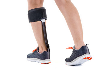 Person in Athletic Sneakers Wearing Brace on Calf.
