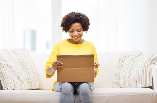happy african young woman with parcel box at home