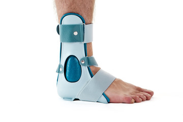 Man Wearing Ankle Support Cast in White Studio.