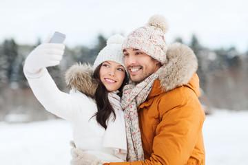 happy couple taking selfie by smartphone in winter
