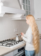 young blonde girl make coffee in turk