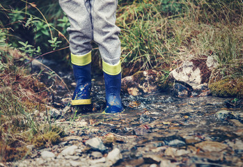 Child legs in gum boots into the forest creek