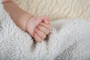 Child's hand clenched into a fist.