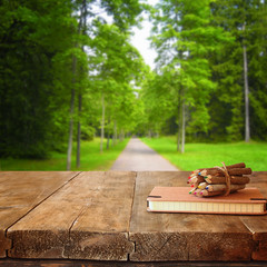 vintage notebook and stack of wooden colorful pencils on wooden texture table in front of summer countryside forest view
