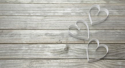Three white hearts on a wood background