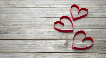 Three red hearts on a wood background