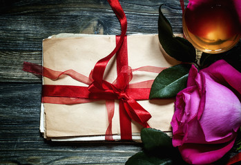 Old letters, tied with a red ribbon on an old wooden background,
