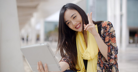 Cheerful beautiful Asian female wearing yellow scarf taking a self portrait and gesturing in front of tablet computer camera