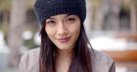 Pretty thoughtful young woman with long brown hair in a woolly cap looking at the camera with a gentle smile  head and shoulders portrait