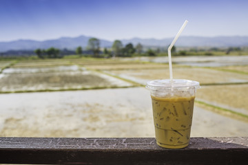 ice coffee, a cup of ice coffee in wood with field, rice, farm and blue sky.