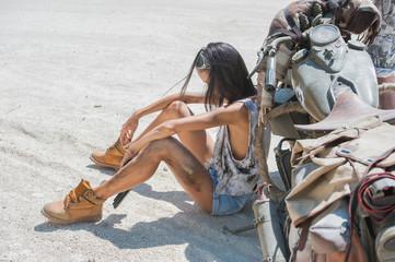 Sexy biker woman on the desert background