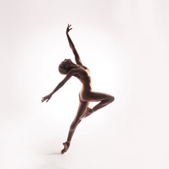 Ballerina in beige outfit posing on toes