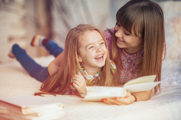 Portrait of a smiling young cute mother and daughter reading a book lying and relax in the bed in a bright big white room
