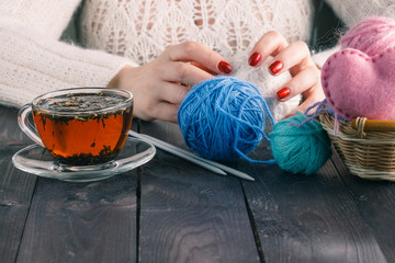 Beautiful girl in a white dress hand knitting with a cup of tea