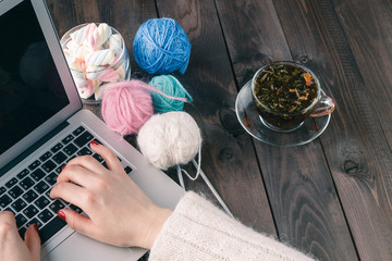woman is knitting in front of laptop