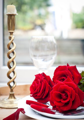 Table setting with red roses on plate - celebrating Valentine's