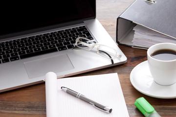 Büro Arbeitsplatz mit Notebook, Kaffee in Tasse, und leerem Papier auf Schreibtisch
