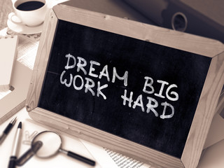 Dream Big Work Hard - Chalkboard with Hand Drawn Text, Stack of Office Folders, Stationery, Reports on Blurred Background. Toned Image. 3d Render.