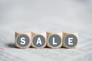 """Würfel mit Wort """"Sale"""" auf einer Zeitung"""