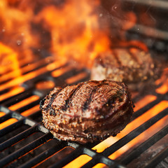 grilling filet mignon steaks on grill with flames