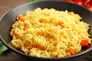 Stewed rice with a carrot on a black plate over wooden background, close up