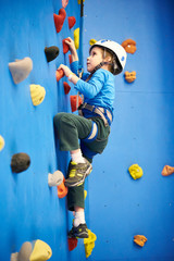 Little boy is climbing on blue wall