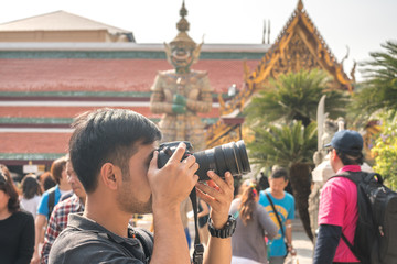 Tourists are taking pictures of Wat Phra Kaew.