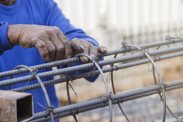 Old hand steel worker man hold steel wire bundle
