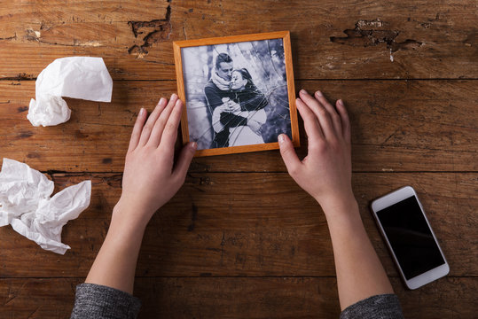 Unrecognizable sad woman holding broken picture of couple in love.
