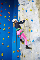 Athlete girl is climbing park on blue wall