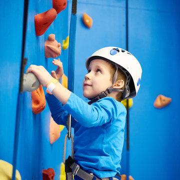 Little boy is climbing in sport park on blue wall