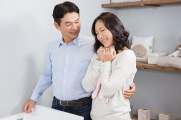 Happy couple holding pink onesie