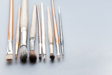 Used, vintage paintbrushes on gray background. macro view different size wooden and textured paint brush, shallow depth of field photography. copy space