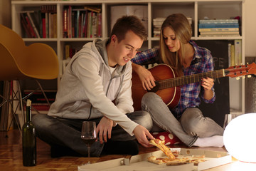 Young couple having fun with music, wine and pizza at home
