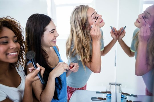 Three smiling friends putting makeup on together