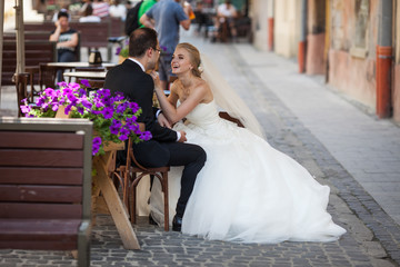Cheerful bride and gromm sitting on wooden chairs in french cafe