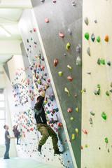 Ragazzo che scala una parete per arrampicata