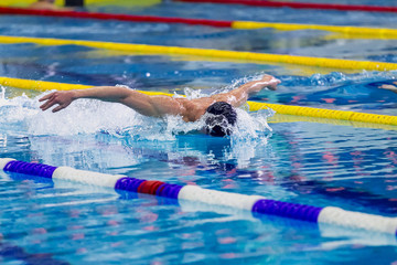 athlete male swimmer swimming in pool butterfly. side view