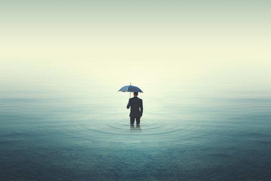 Wet business man walking into water