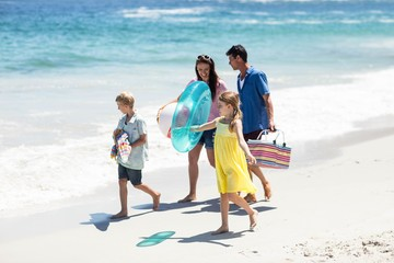 Cute family holding beach equipment