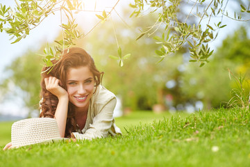 Beautiful smiling woman lying on a grass outdoor.