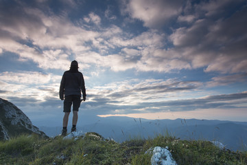 Man meditatidng over mountain and clouds