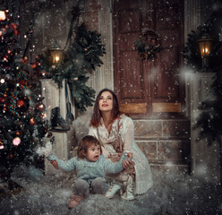 little girl smiles and enjoys the snow sitting by the mother's arms bear , happy childhood , fashionable toning , creative color.