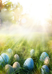 Fototapete - art Colorful Easter eggs in the grass on sky background