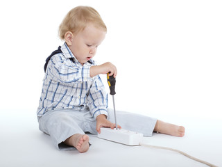 boy plays with plug and screwdriver