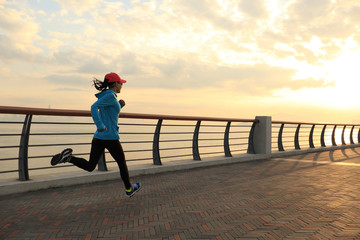 young fitness woman runner running at sunrise seaside Wall mural