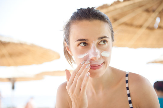beautiful woman smears face sunscreen at the beach for protection