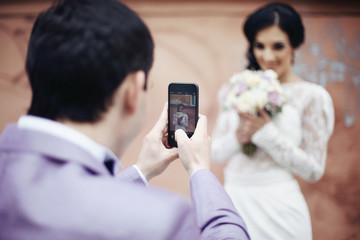 Handsome groom taking photo of beautiful bride on his phone