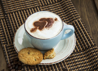 Cappuccino latte coffee with cocoa heart-shape and cookies